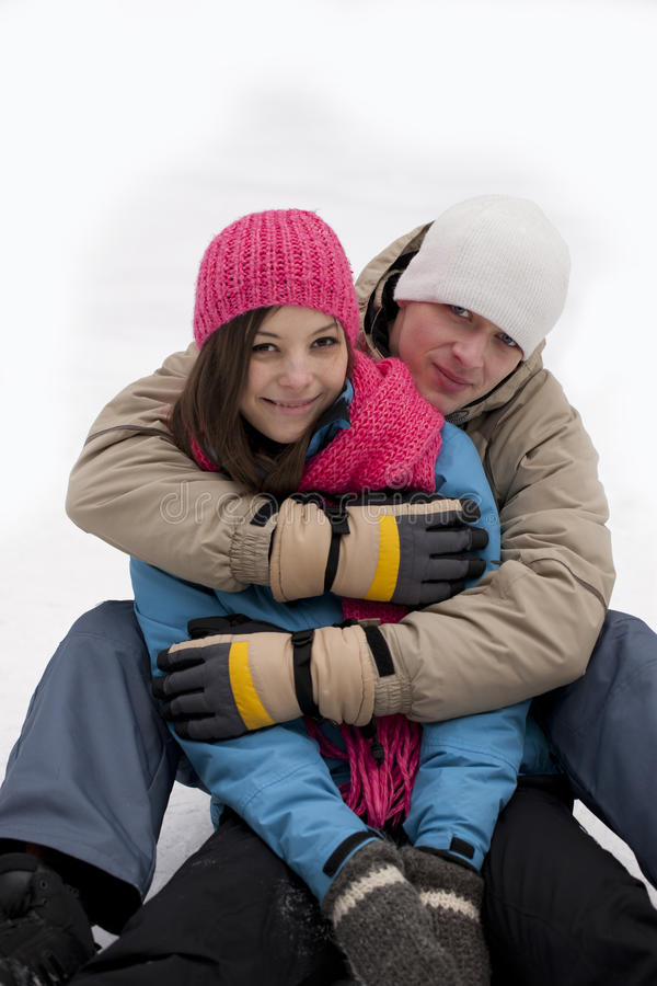 Winter couple sitting on the snow. Young happy smiling couple sitting on the snow stock photos