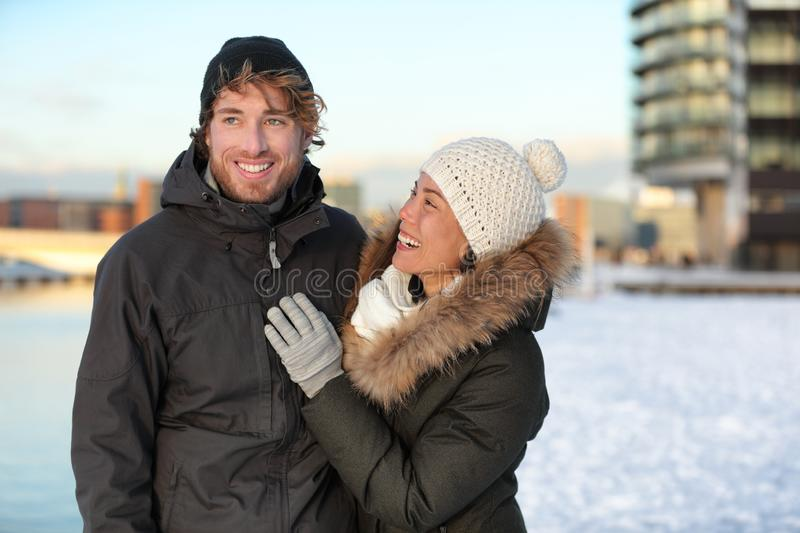 Winter couple walking in snow with hat and coats stock photos