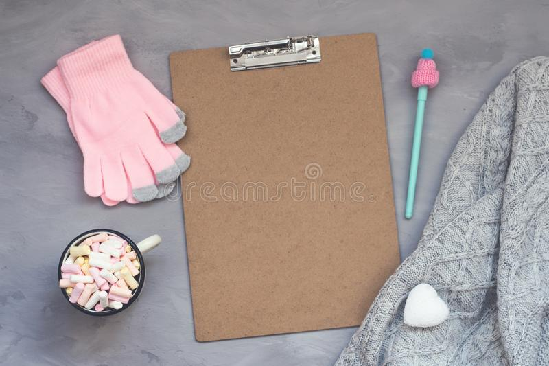 Winter cozy clipping board mockup, banner. Coffee with marshmallows, knitted sweater, white heart, pen with cap and pink gloves on. Grey cement background. Flat stock photos