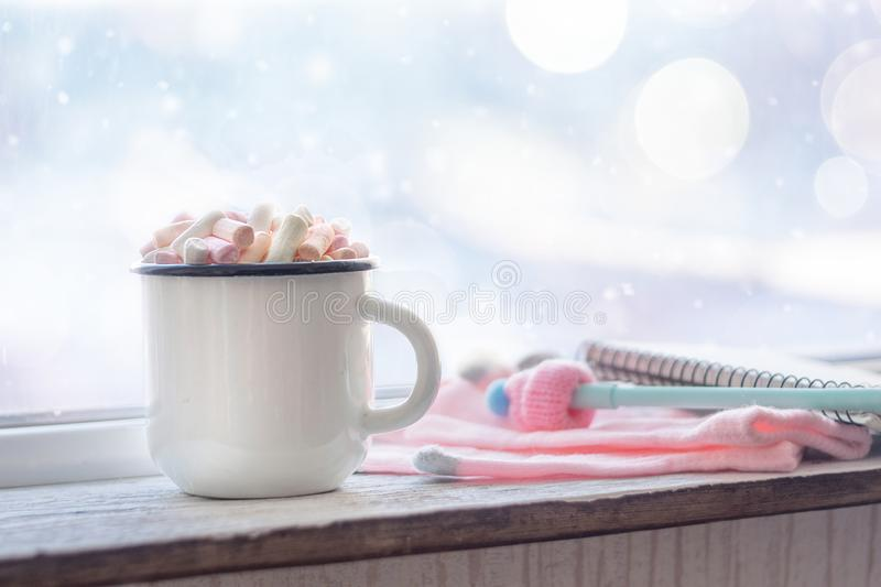 Winter cozy concept. Coffee with marshmallows, pen with cap and pink gloves near window sill with the snow-covered window bokeh. Warm weekend in cold weather royalty free stock image