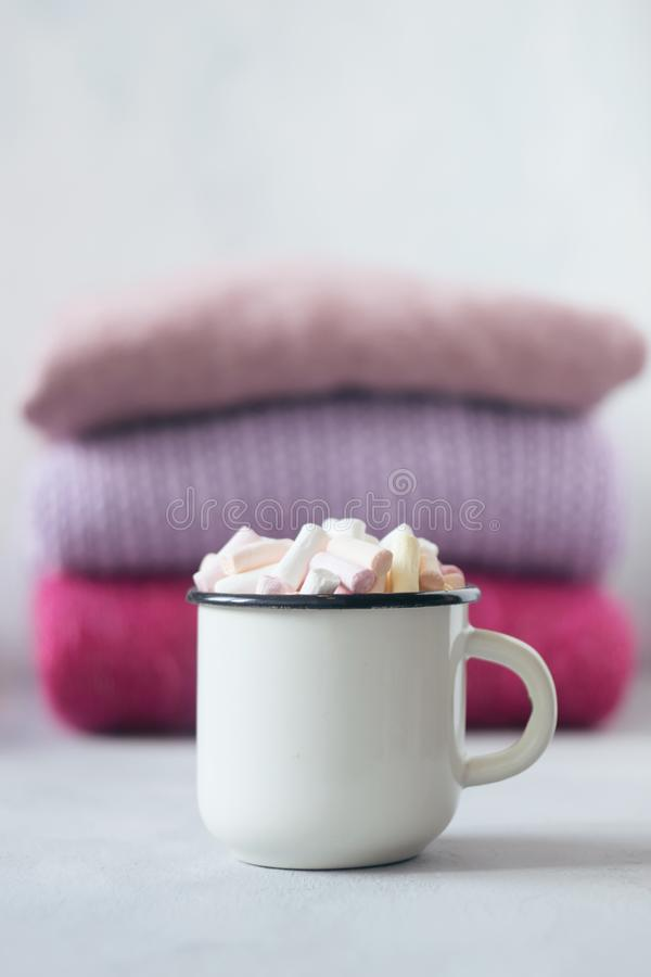 Winter cozy concept. Sweater weather. Coffee with marshmallows in white enameled metal cup on the background of stack of pink. Knitted sweaters on table. Warm stock photo