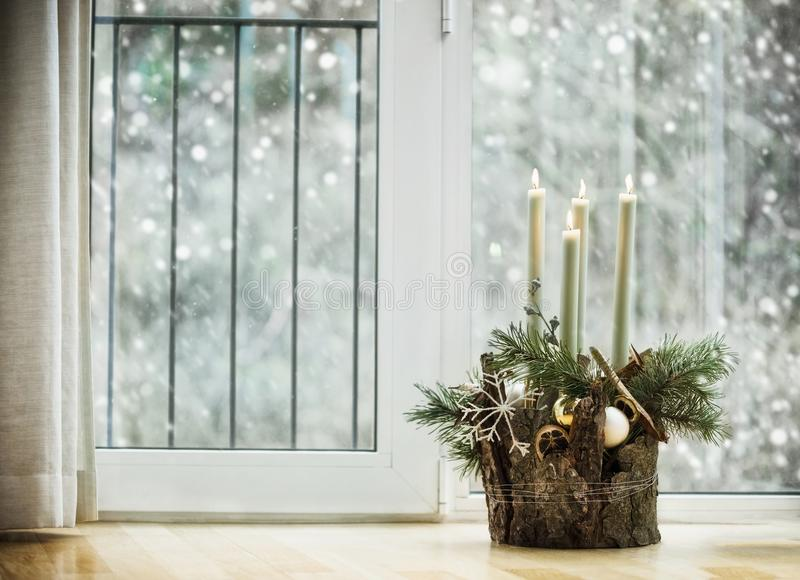 Winter cozy home decoration and festive holiday atmosphere with burning candles. Fir branches and snowflakes in living room at window with snowfall. Decorated stock photo