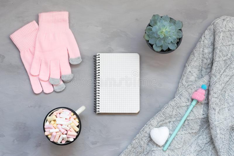 Winter cozy mockup, banner. Open paper notepad, Coffee with marshmallows, knitted sweater, white heart, pen with cap and pink. Gloves on grey cement background stock photography