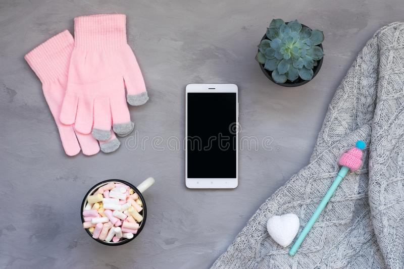 Winter cozy mockup, banner. White smartphone, Coffee with marshmallows, knitted sweater, white heart, pen with cap and pink gloves. On grey cement background stock images