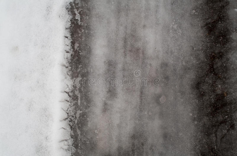Winter dark melted snow background. Melted snow on the road in winter background royalty free stock photos