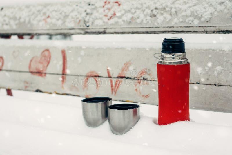 Winter-Datums-Ideen für Paare Winterurlaube, heißes Getränkkonzept Thermosflasche und Schalen auf einer schneebedeckten Bank im W lizenzfreies stockfoto