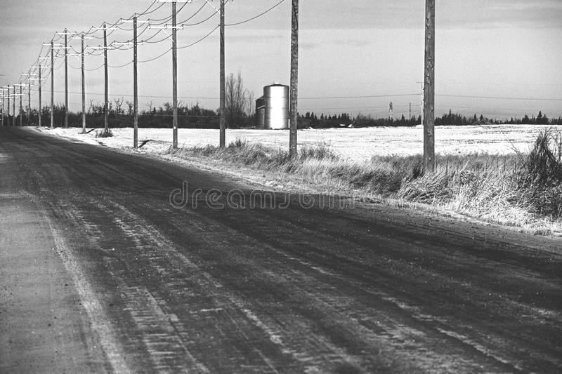 Long road in the muddle of no where. Winter day, down a dirt road and the farmers fields stock photos
