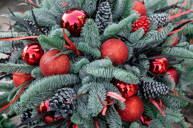 Winter decor. Beautiful arrangement of christmas tree red balls, cones, natural spruce branches for indoor outdoor festive royalty free stock photo