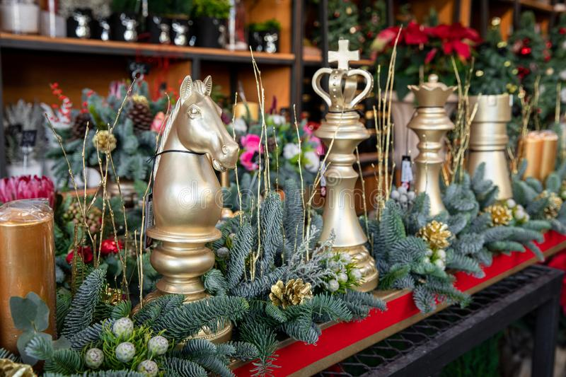 Winter decor. Beautiful arrangement of golden chess pieces, natural spruce branches, golden cones for luxury Christmas New Year royalty free stock images