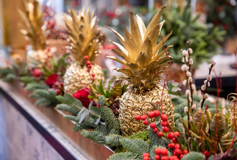 Winter decor. Beautiful arrangement of golden colored pineapples, red roses, natural sprigs of blue spruce and Christmas berry royalty free stock image