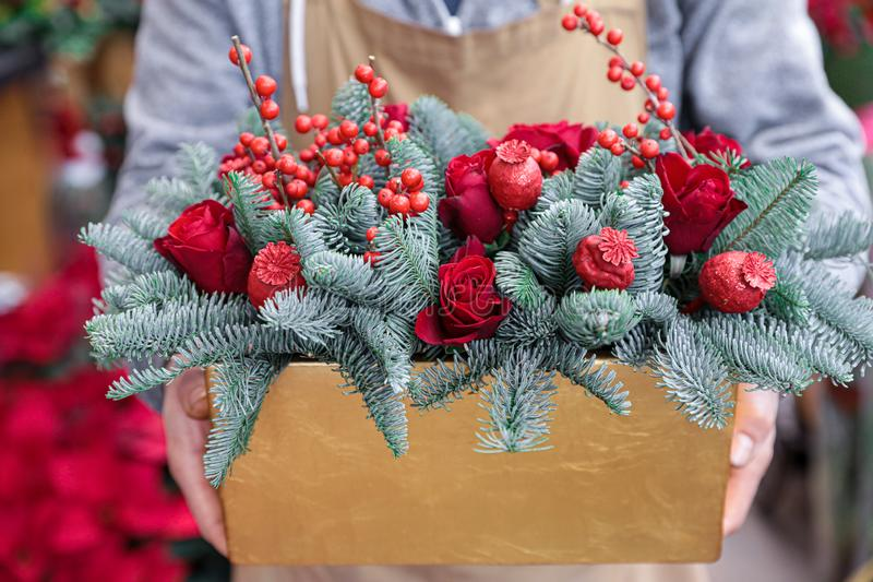 Winter decor. Beautiful flower arrangement of red roses, natural sprigs of blue spruce and Christmas berry holly or ilex twigs,. Brightly colored poppy heads stock image