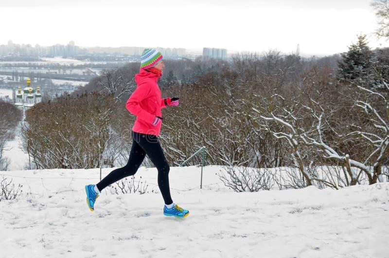 Winter, der in Park läuft: glücklicher aktiver Frauenläufer, der im Schnee mit Kyiv-Stadt-Skylineansicht, Sport im Freien und Eig lizenzfreies stockbild