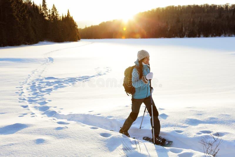 Winter die snowshoeing Sporttätigkeitsfrau wandernd stockbilder