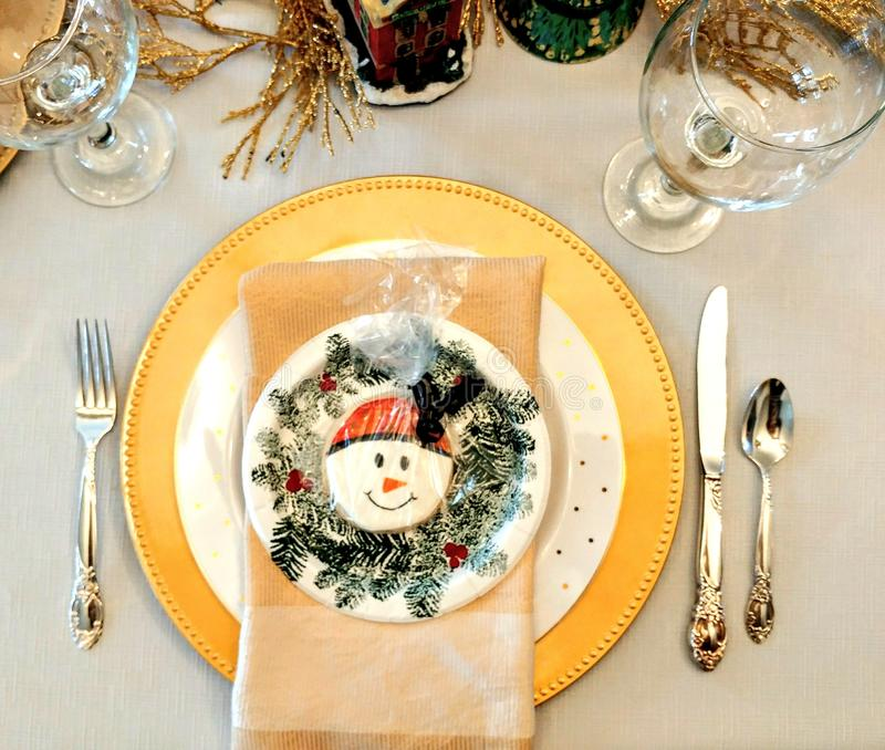 Winter Dinner Table Setting with Snowman. A winter dinner table setting with plates, fork, knife, spoon, silverware, wine glasses and a snowman cookie in the stock photos