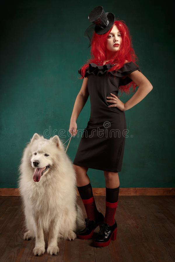 Winter dog holiday and Christmas. Girl in a black dress and with red hair with a pet in the studio. Christmas woman with royalty free stock photos