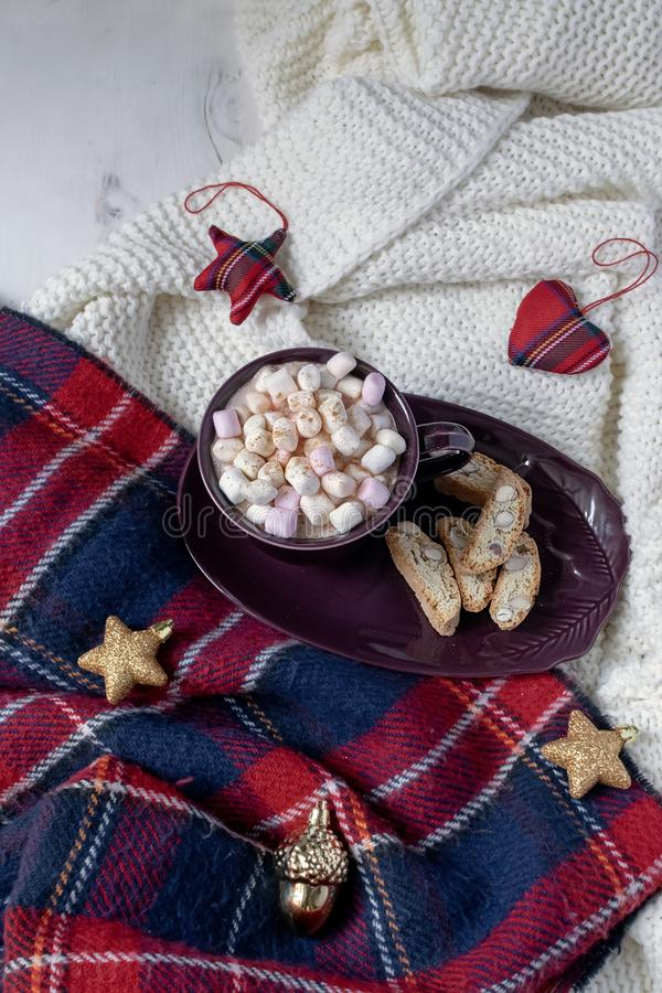 Winter drink flat lay - hot chocolate with marshmallows, red and gold deco baubles, garland, knitted checkered plaid, hygge style. Winter drink flat lay - hot stock photography