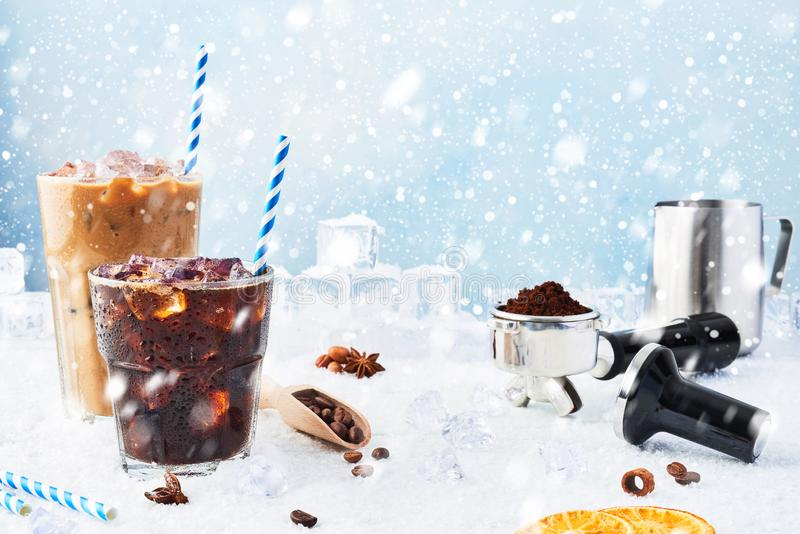 Winter drink iced coffee in a glass and ice coffee with cream in a tall glass surrounded by ice. Barista concept royalty free stock photo
