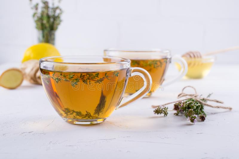 Winter drink. Warming hot tea with lemon, ginger, and herbs thyme, stock photos