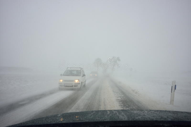 Winter driving by blizzard royalty free stock image