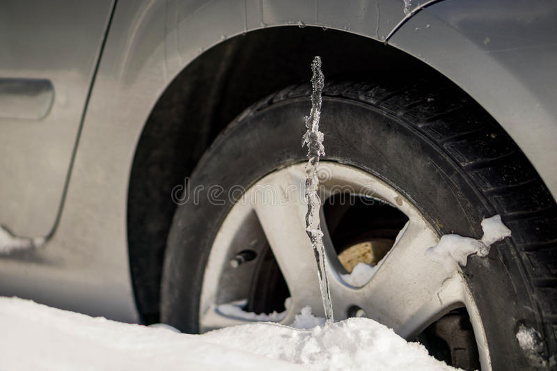 Winter driving problems, snow and ice. Extreme winter series. Huge icicles on the dirty car wheel. Dangerous ice build up car stock image
