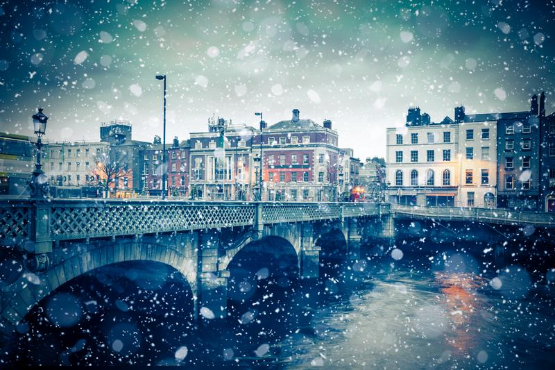 Winter Dublin Ireland Snow Bridge. Evening view of Dublin Ireland at the Grattan Bridge of the River Liffey with snowflakes falling during winter snow storm royalty free stock photography