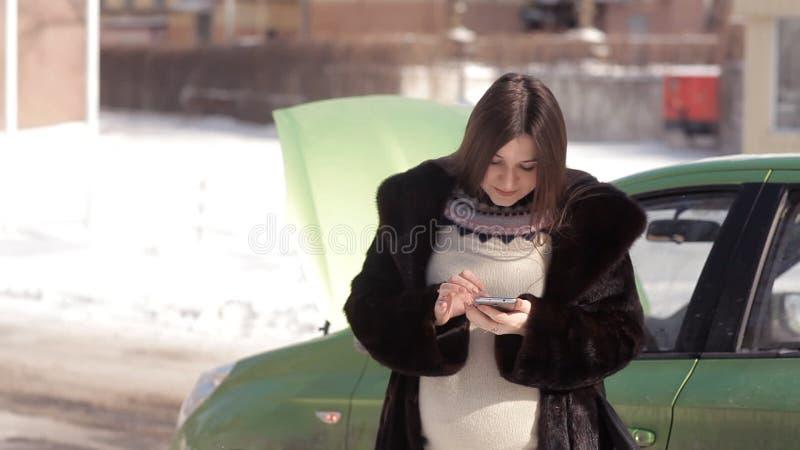 In winter, een zwanger meisje, die de zich dichtbij een defecte auto met een open kap bevinden, die een slepenvrachtwagen met een stock footage