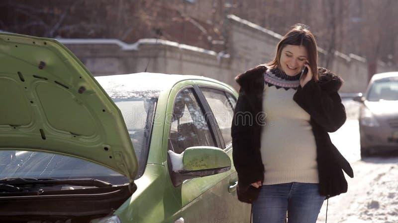 In winter, een zwanger meisje, die de zich dichtbij een defecte auto met een open kap bevinden, die een slepenvrachtwagen met een stock video