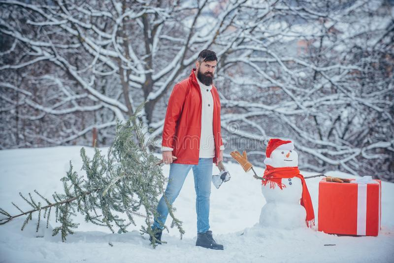 Winter emotion. Young woodcutter winter portrait. Man is going to cut a Christmas tree. Bearded man with freshly cut royalty free stock images