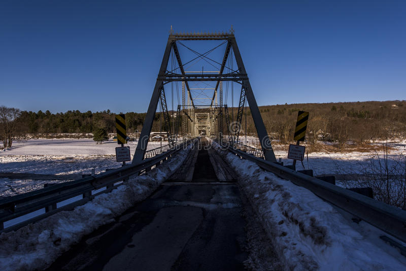 Winter Evening Scene at Historic Skinners Fall Truss Bridge. An evening winter scene of the historic one-lane Skinners Fall truss Bridge over the Delaware River royalty free stock photos