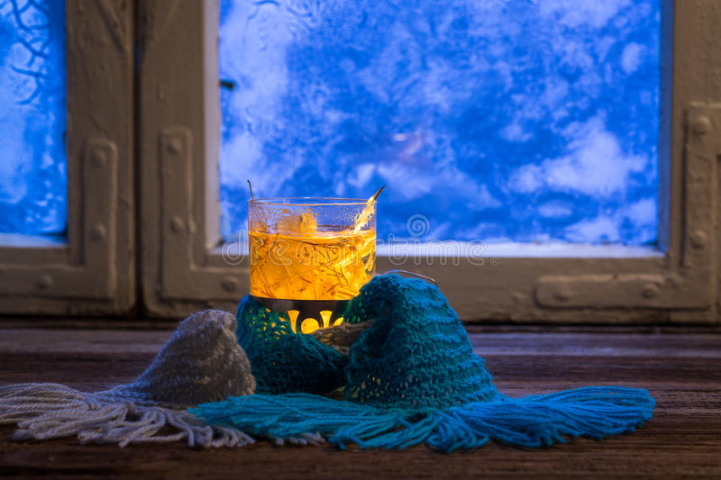 Winter evening with warming tea. At frozen window royalty free stock image