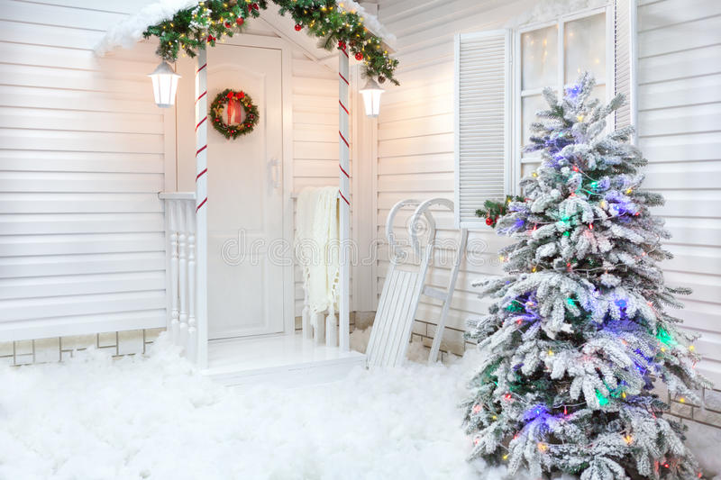 Winter exterior of a country house with Christmas decorations in the American style. Snow-covered courtyard with a porch, tree and wooden vintage sleds stock image
