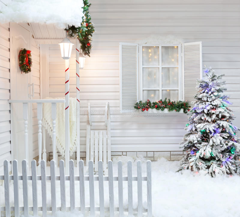 Winter exterior of a country house with Christmas decorations in the American style. Snow-covered courtyard with a porch, tree and wooden vintage sleds stock photography