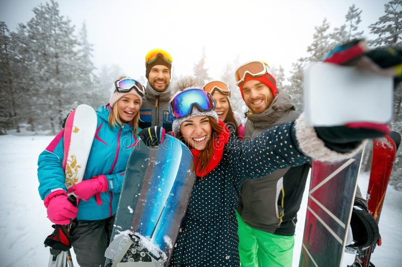 Winter, extreme sport and people concept - Group of smiling friends making selfie. On the snow royalty free stock photos