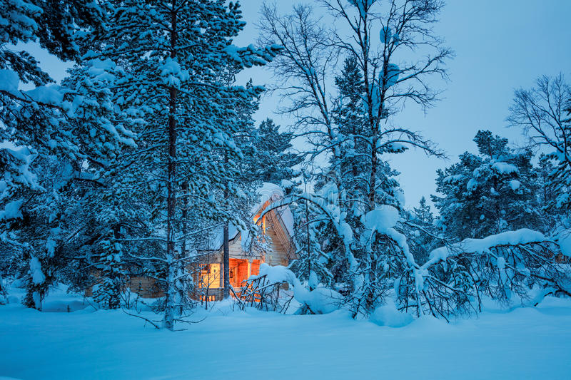 Winter fairy night - wooden house in blue snowy forest. Winter fairy night - wooden cottage with warm light in blue snowy forest, silent winter weather. Seasonal royalty free stock images