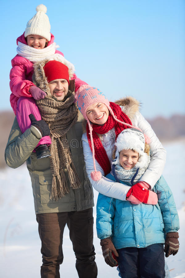 Winter family. Happy parents with kids in winterwear looking at camera outside stock images