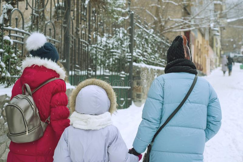 Winter family walk in the city, the mother and her daughters walk along the snow-covered city street, the view from the back royalty free stock photos