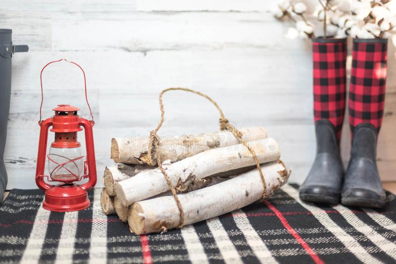 Winter farmhouse background with boots, logs and lantern stock photo