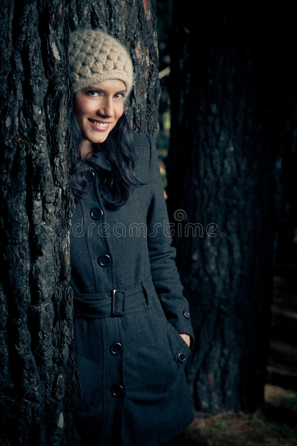 Winter fashion. Woman with a coat and beany standing in a forest stock photography