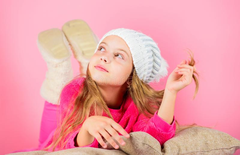 Winter fashion accessory. Winter accessory concept. Girl long hair dream pink background. Kid girl knitted hat. Kid. Dreamy lean on pillows. Winter season royalty free stock image