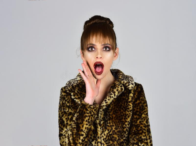 Winter fashion and beauty. Woman in leopard fur coat on grey background. Fur coat boutique with natural and artificial. Material. Look of fashion model with bad stock photography