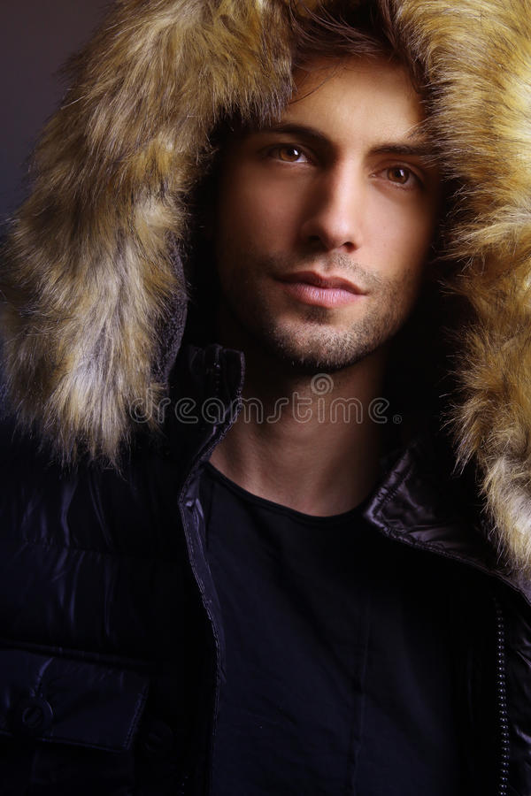 Winter fashion .Handsome man wearing fur hood royalty free stock images