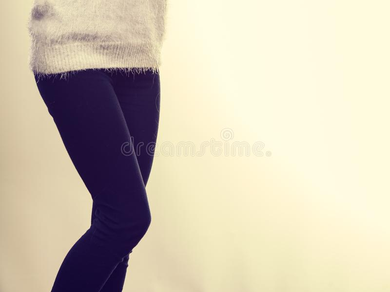 Woman legs in black trousers and furry jumper. Winter fashion, outfit ideas concept. Woman legs in black leggings trousers and grey furry jumper royalty free stock image