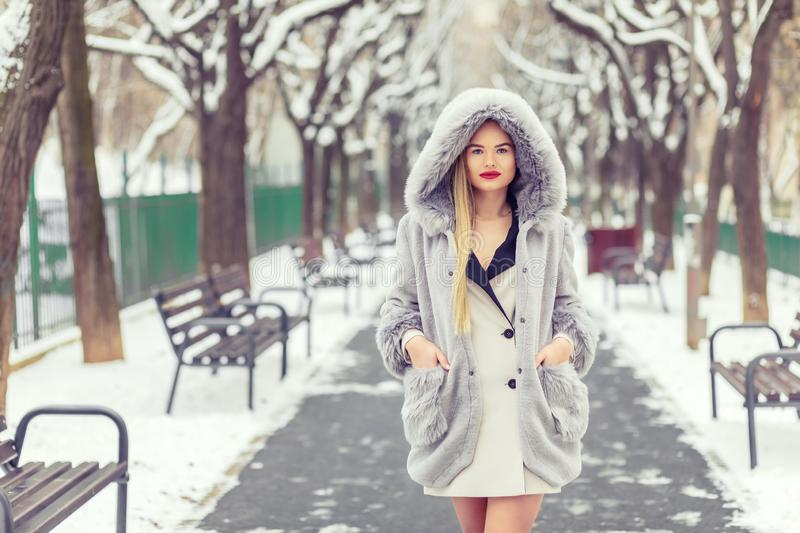 Winter fashion portrait of blonde woman wearing fashionable coat and fur hat walking in snow park stock image