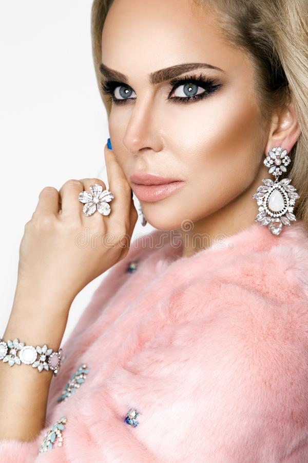Winter Fashion Style. Beautiful Woman In pink Fur And Jewelry. Portrait Of Young Sexy Model With Beauty Makeup On Gorgeous Face In royalty free stock image