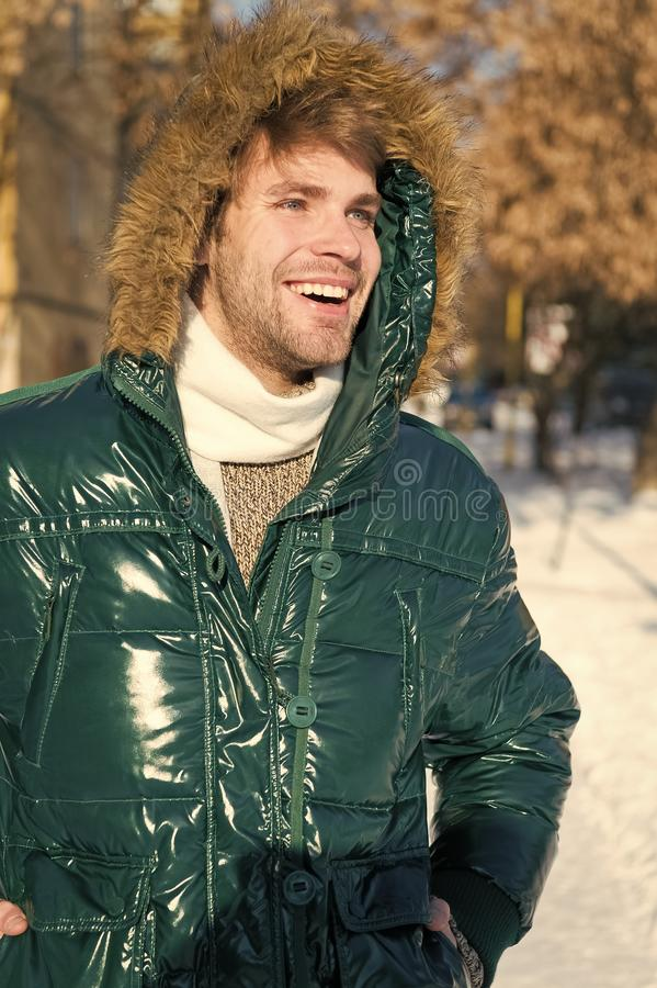 Winter fashion. Warm clothes. Happy man on winter holidays. Snowy weather. Trendy winter coat. Vacation and traveling in stock photography