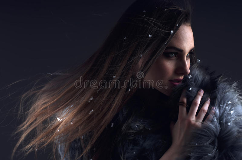 Winter fashion woman in a fur coat. Winter fashion woman in a fur coat over dark background royalty free stock photography