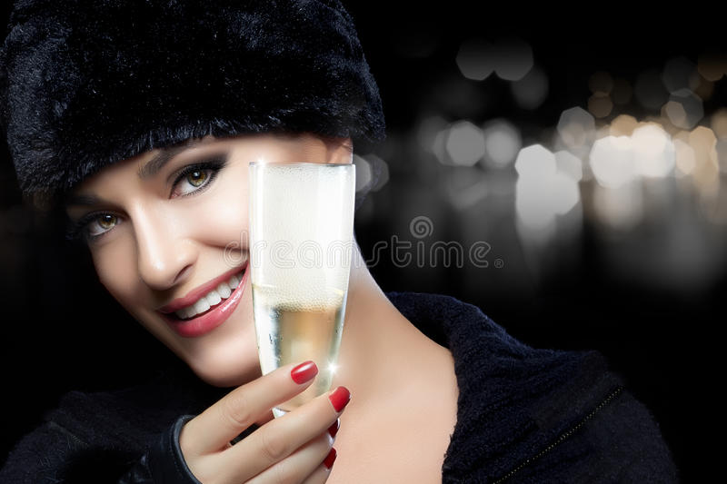 Winter Fashion Young Woman in Fur Hat Toasting with Champagne stock photography