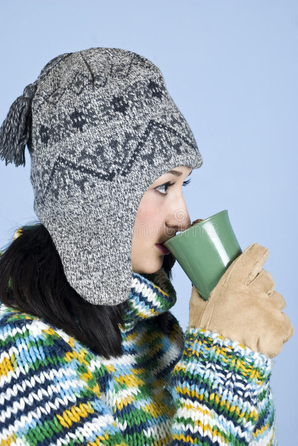 Winter female drinking a cup of tea. Teen female drinking a cup of hot tea and standing in profile in front of blue background,check also my collection royalty free stock photography