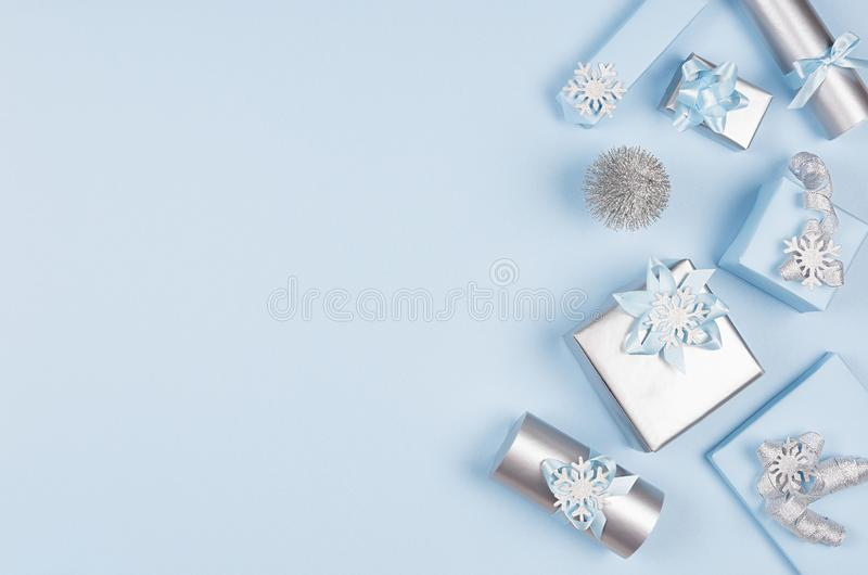 Winter festive background for advertising and design - set of blue and silver metallic gift boxes with ribbons on soft blue. royalty free stock photos