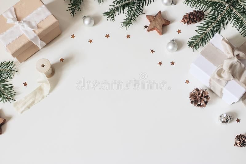 Winter festive frame composition. Pine cones, silk ribbons, fir tree branches, gift wrapped boxes, Christmas balls royalty free stock photos